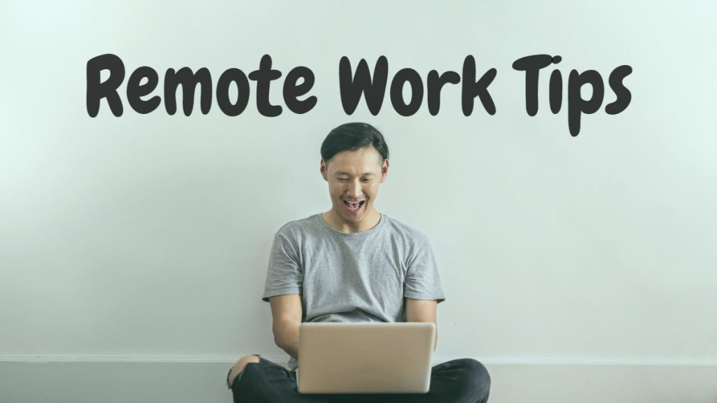 """Remote Work Tips"" text on wall with man sitting below on his computer and smiling."
